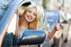 Mujer en el coche que da los pulgares para arriba Fotos de archivo libres de regalías