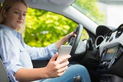 Mujer en el coche que manda un SMS en el teléfono móvil mientras que conduce Foto de archivo