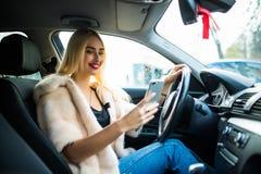Mujer en el coche que manda un SMS en el teléfono móvil mientras que conduce en la ciudad Fotografía de archivo libre de regalías
