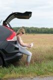 Mujer en el coche que mira el mapa Imagen de archivo