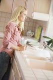 Mujer en el contador de cocina Foto de archivo libre de regalías