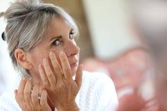 Mujer en el cuarto de baño que toma el cuidado de la piel Fotos de archivo