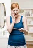 Mujer en el cuarto de baño que ve la prueba de embarazo positiva fotografía de archivo libre de regalías