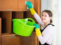 Mujer en el delantal que limpia en casa Foto de archivo libre de regalías
