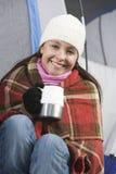 Mujer en el desgaste del invierno que sostiene la taza de café Imagen de archivo