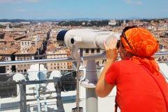 Mujer en el desgaste rojo que mira a través de los prismáticos Imagenes de archivo