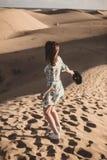 Mujer en el desierto en ella detr?s con un tel?fono m?vil en su mano foto de archivo libre de regalías