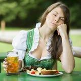 Mujer en el dirndl que se sienta en jardín y sueños de la cerveza Imagen de archivo libre de regalías