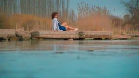 Mujer en el embarcadero por el río almacen de metraje de vídeo