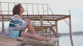 Mujer en el embarcadero por el río almacen de video