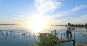 Mujer en el embarcadero por el río en la puesta del sol almacen de video