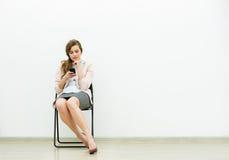 Mujer en el equipo de la oficina que espera en una silla foto de archivo