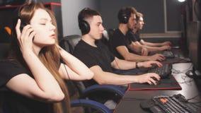 Mujer en el equipo de videojugadores del eSport que juegan a los videojuegos en una competencia cibernética de los juegos almacen de metraje de vídeo