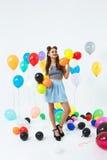 Mujer en el equipo elegante que presenta con los globos en el partido brillante Imagenes de archivo