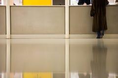 Mujer en el escritorio del Info en aeropuerto Imagen de archivo libre de regalías