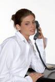Mujer en el escritorio en el teléfono imagenes de archivo
