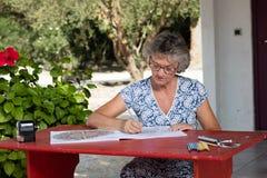 Mujer en el escritorio rojo Foto de archivo libre de regalías