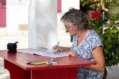 Mujer en el escritorio rojo Imagen de archivo