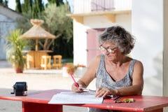 Mujer en el escritorio rojo Imagenes de archivo
