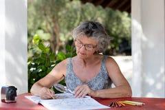 Mujer en el escritorio rojo Fotos de archivo
