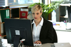 Mujer en el escritorio usando el ordenador Imagen de archivo