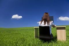 Mujer en el escritorio y el ordenador de oficina en campo verde Imágenes de archivo libres de regalías