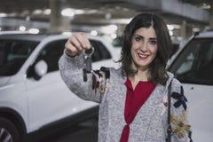 Mujer en el estacionamiento del coche que muestra llaves y la sonrisa del vehículo Imagen de archivo