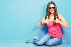 Mujer en el estilo de la juventud que se sienta en un piso Imagen de archivo libre de regalías