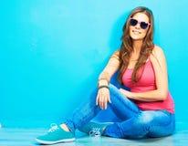 Mujer en el estilo de la juventud que se sienta en un piso Fotografía de archivo