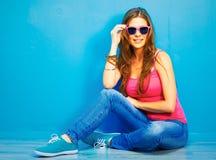Mujer en el estilo de la juventud que se sienta en un piso Fotos de archivo