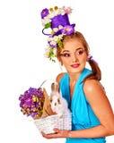 Mujer en el estilo de pascua que sostiene el conejito y las flores Imágenes de archivo libres de regalías
