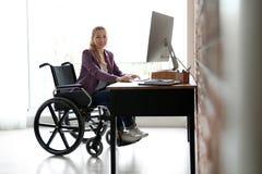 Mujer en el funcionamiento de la silla de ruedas con el ordenador en la tabla imagenes de archivo