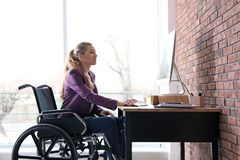 Mujer en el funcionamiento de la silla de ruedas con el ordenador en la tabla foto de archivo libre de regalías