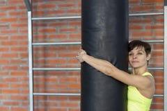 Mujer en el gimnasio con un saco de arena imagen de archivo libre de regalías