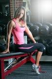 Mujer en el gimnasio en un banco Foto de archivo