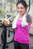 Mujer en el gimnasio que come un plátano Foto de archivo libre de regalías