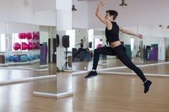 Mujer en el gimnasio, salto del ejercicio imagenes de archivo