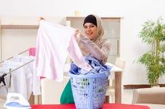 Mujer en el hijab que hace la ropa que plancha en casa fotos de archivo libres de regalías