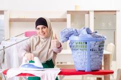 Mujer en el hijab que hace la ropa que plancha en casa imagen de archivo libre de regalías