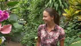 Mujer en el jardín tropical que mira en mariposa almacen de metraje de vídeo