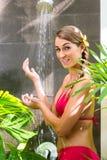 Mujer en el jardín tropical que tiene ducha Foto de archivo
