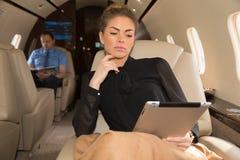 Mujer en el jet corporativo que mira la tableta imagen de archivo