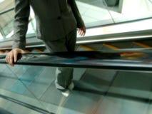 Mujer en el juego que va para arriba la escalera móvil Foto de archivo libre de regalías