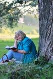 Mujer en el libro de lectura del árbol del parque Imagen de archivo libre de regalías