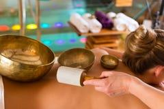 Mujer en el masaje de la salud con los tazones de fuente del canto Foto de archivo libre de regalías