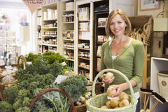 Mujer en el mercado que mira la sonrisa de las patatas Fotos de archivo