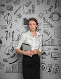 Mujer en el muro de cemento con bosquejos del negocio Fotografía de archivo libre de regalías