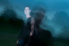 Mujer en el negro cubierto en oscuridad y misterio Foto de archivo libre de regalías
