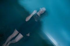 Mujer en el negro cubierto en oscuridad y misterio Foto de archivo