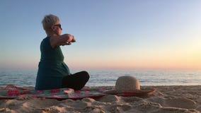 Mujer en el noveno mes del embarazo excercising en la playa metrajes